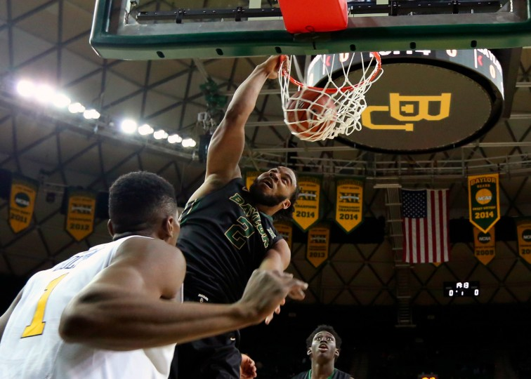 Baylor forward Rico Gathers (2) dunks over West Virginia forward Jonathan Holton (1) in the first half of an NCAA college basketball game in Waco, Texas. Baylor won 78-66. (Rod Aydelotte/Associated Press)