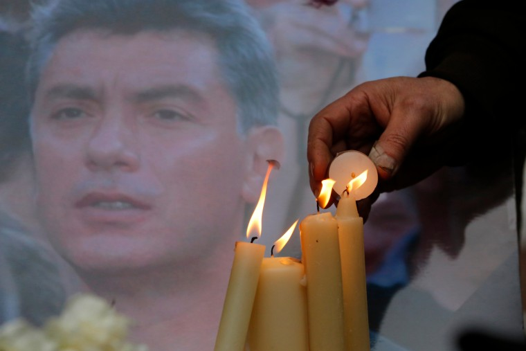People light candles in memory of Boris Nemtsov, seen behind, at the monument of political prisoners 'Solovetsky Stone' in central St.Petersburg, Russia. Nemtsov was gunned down Saturday near the Kremlin, just a day before a planned protest against the government. (Dmitry Lovetsky/Associated Press)