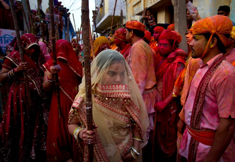 Indian Hindu women from Nandgaon village with their wooden sticks wait for men from Barsana village during Lathmar holi festival celebrations in Nandgaon, India. During Lathmar Holi the women of Nandgaon, the hometown of Krishna, beat the men from Barsana, the legendary hometown of Radha, consort of Hindu God Krishna, with wooden sticks in response to their teasing as they depart the town. (Saurabh Das/Associated Press)