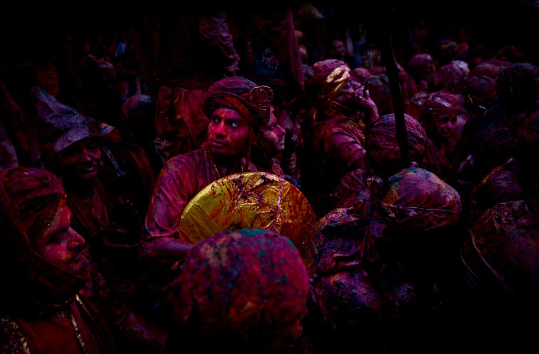 Indian Hindu devotees smeared with colors visit the Nandagram temple, famous for Lord Krishna and his brother Balram, during Lathmar holi festival, in Nandgaon, India. During Lathmar Holi the women of Nandgaon, the hometown of Krishna, beat the men from Barsana, the legendary hometown of Radha, consort of Hindu God Krishna, with wooden sticks in response to their teasing as they depart the town. (Saurabh Das/Associated Press)