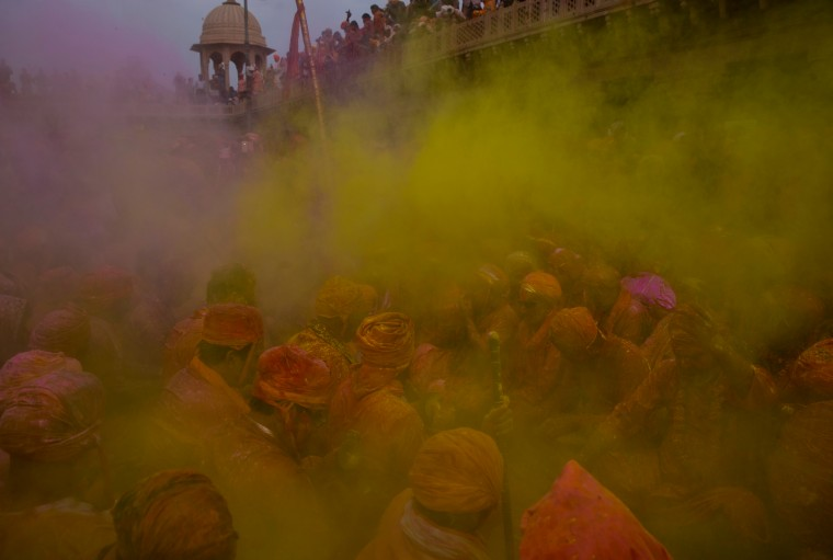 Indian Hindu devotees smeared with colors, sing songs at the Nandagram temple famous for Lord Krishna and his brother Balram, during Lathmar holi festival, in Nandgaon, India. During Lathmar Holi the women of Nandgaon, the hometown of Krishna, beat the men from Barsana, the legendary hometown of Radha, consort of Hindu God Krishna, with wooden sticks in response to their teasing as they depart the town. (Saurabh Das/Associated Press)