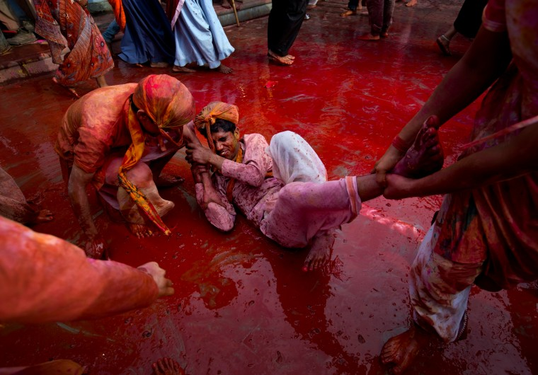 Indian Hindu men smeared with colors play holi during Lathmar festival celebrations in Nandgaon, India. During Lathmar Holi the women of Nandgaon, the hometown of Krishna, beat the men from Barsana, the legendary hometown of Radha, consort of Hindu God Krishna, with wooden sticks in response to their teasing as they depart the town. (Saurabh Das/Associated Press)
