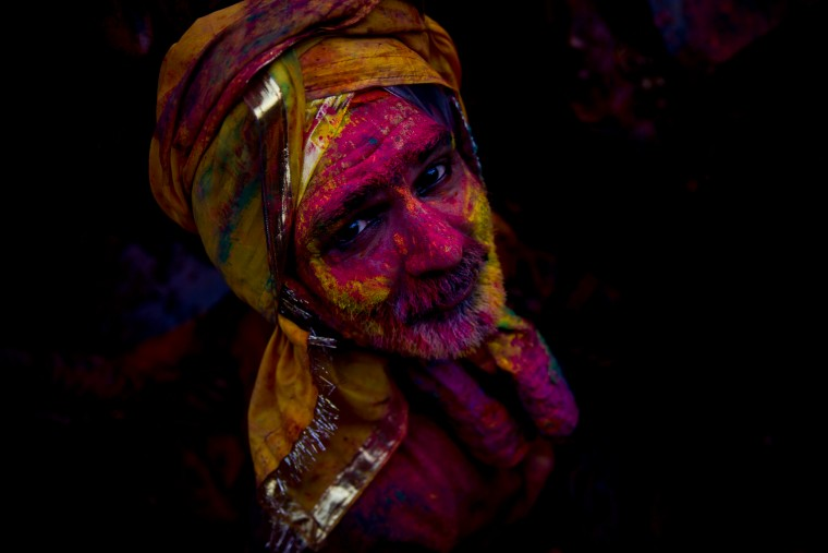 A Hindu devotee smeared with colors watches as he visits the Nandagram temple, famous for Lord Krishna and his brother Balram, during Lathmar holi festival, in Nandgaon, India. During Lathmar Holi the women of Nandgaon, the hometown of Krishna, beat the men from Barsana, the legendary hometown of Radha, consort of Hindu God Krishna, with wooden sticks in response to their teasing as they depart the town. (Saurabh Das/Associated Press)