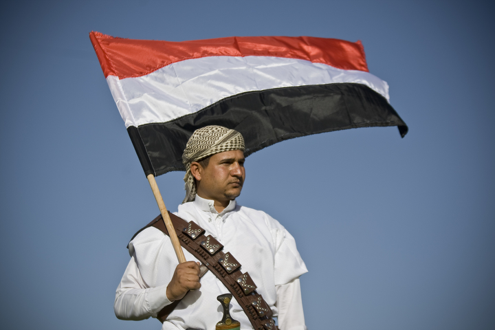 "A supporter of Houthi Shiites, who took over the government of Yemen and installed a new committee to govern, holds a Yemeni flag during a rally in support of the Houthis, at a sports stadium in Sanaa, Yemen. A group of Gulf countries denounced the Shiite rebel takeover of Yemen as a ""coup"" Saturday, calling for the United Nations to take action as thousands demonstrated in the streets against their power grab. (Hani Mohammed/Associated Press)"