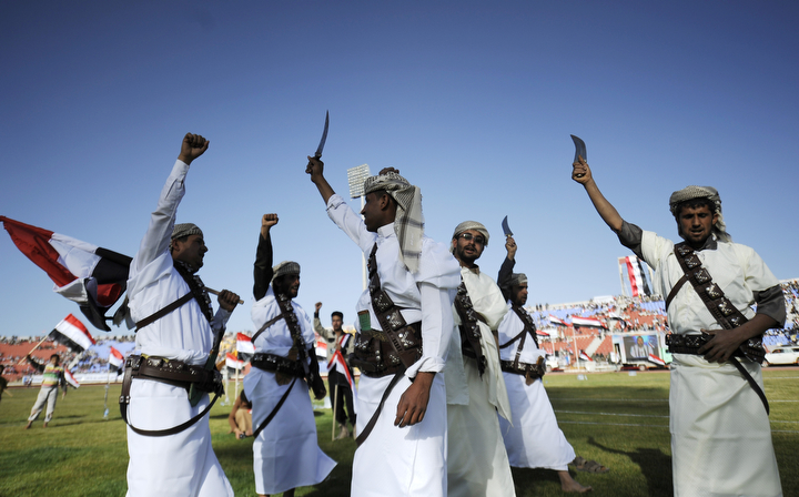 "Supporters of Houthi Shiites, who took over the government of Yemen and installed a new committee to govern, wave traditional daggers and chant slogans at a rally in support of the Houthis, at a sports stadium in Sanaa, Yemen. A group of Gulf countries denounced the Shiite rebel takeover of Yemen as a ""coup"" Saturday, calling for the United Nations to take action as thousands demonstrated in the streets against their power grab. (Hani Mohammed/Associated Press)"