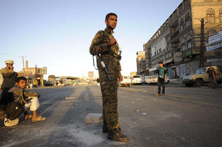 "A Houthi Shiite fighter wearing an army uniform, stands guard outside of a sports stadium during a rally in Sanaa, Yemen,. A group of Gulf countries denounced the Shiite rebel takeover of Yemen as a ""coup"" Saturday, calling for the United Nations to take action as thousands demonstrated in the streets against their power grab. (Hani Mohammed/Associated Press)"