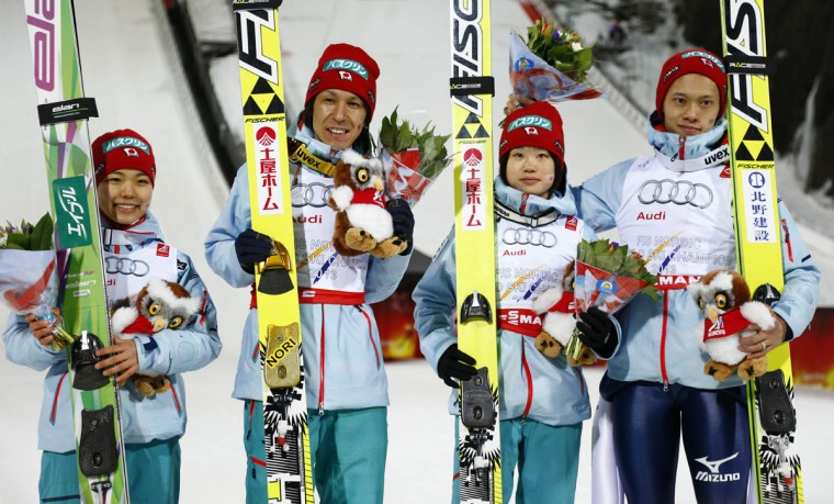 Japan teammates pose for photographers after they captured the third place during the Mixed Team Ski Jumping competition at the Nordic Skiing World Championships in Falun, Sweden, Sunday, Feb. 22, 2015. (AP Photo/Matthias Schrader)