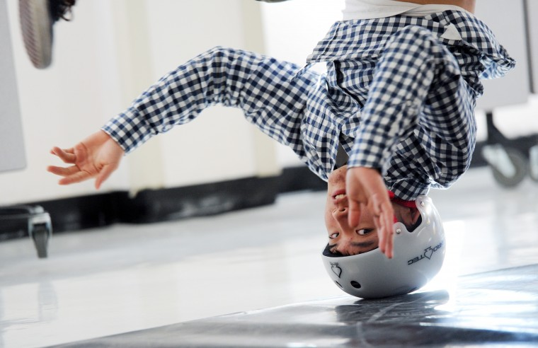 John Oh, 16, a junior and co-captain of the Mt. Hebron Break Dance team, practices a head spinning move in the school cafeteria, Tuesday, Feb. 3, 2015. Oh says the helmet is for safety, but most pros wear them to prevent balding. (Jon Sham/BSMG)