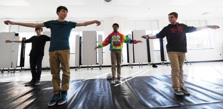 From left, Mt. Hebron Break Dance team members Garrett Collins, 14, a freshman, Mitchell Cohen, 14, a freshman, Khalif Green, 17, a senior, and Paul Riggins, 17, a senior and team co-captain, practice a synchronized part of their routine, Tuesday, Feb. 3, 2015 in the school cafeteria. (Jon Sham/BSMG)