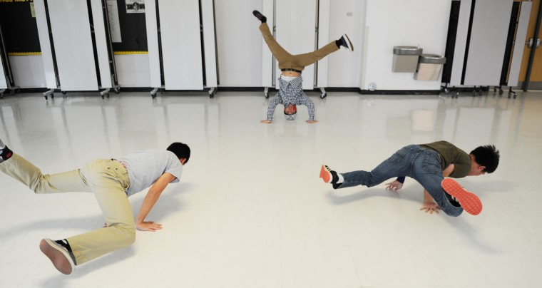 From left, Mt. Hebron Break Dance team members Andrew Park, 17, a senior, John Oh, 16, a junior and co-captain, and Alex Cha, 17, a senior, practice their routine Tuesday, Feb. 3, 2015 in the school cafeteria. (Jon Sham/BSMG)