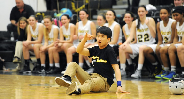 The Mt. Hebron girls basketball team watches John Oh, 16, break dance during halftime of the team's game against Centennial, Thursday, Feb. 19, 2015 in Ellicott City. (Jon Sham/BSMG)