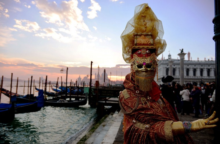 A costumed reveler poses in front of gondolas during the Venice Carnival on February 8, 2015 in Venice. (VINCENZO PINTO/AFP/Getty Images)