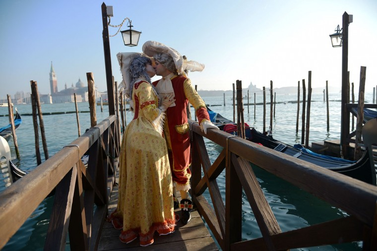 Costumed revelers kiss in front of gondolas at St Mark's square (Piazza San marco) during the Venice Carnival on February 8, 2015 in Venice. (VINCENZO PINTO/AFP/Getty Images)