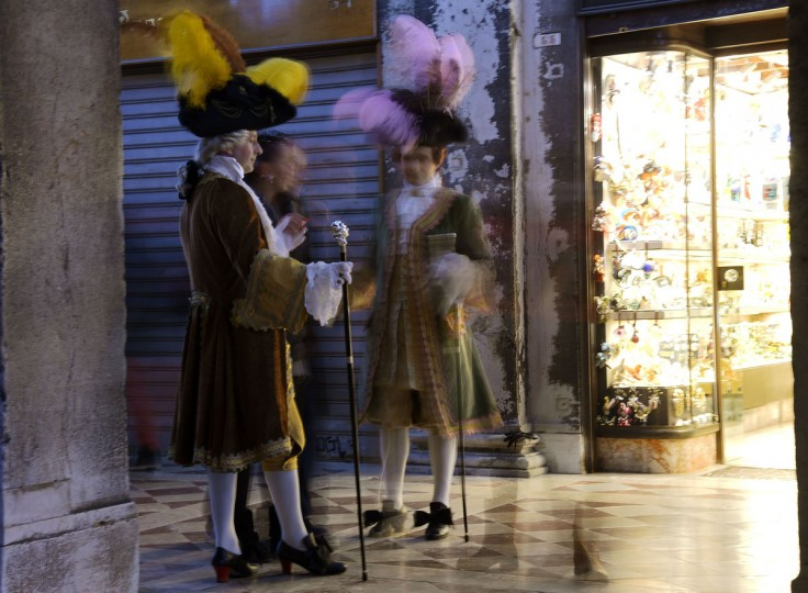 """Costumed revelers walk at St Mark's square (Piazza San marco) during the Venice Carnival on February 8, 2015 in Venice. The 2015 edition of the Venice carnival is called """"The world's most delicious festival"""" and runs until February 17th. (VINCENZO PINTO/AFP/Getty Images)"""