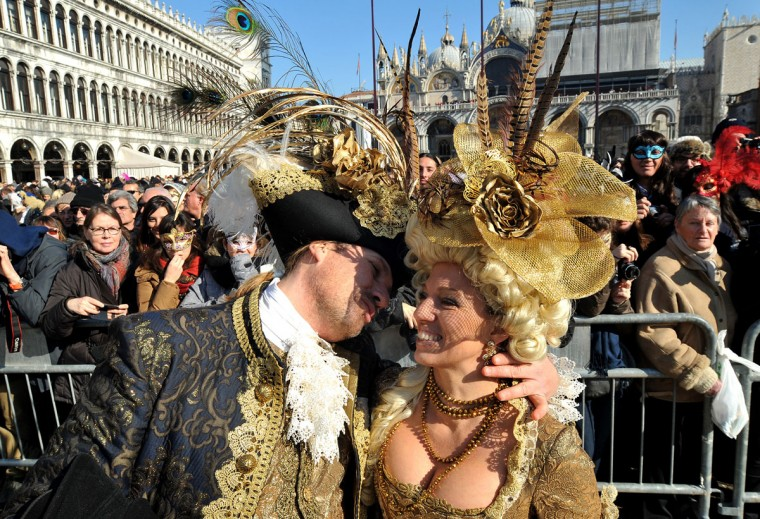A couple wearing traditional costumes parades in St. Mark's square in Venice, Italy, Sunday, Feb. 8, 2015, on the occasion of the Venice Carnival. (AP Photo/Sebastiano Casellati)