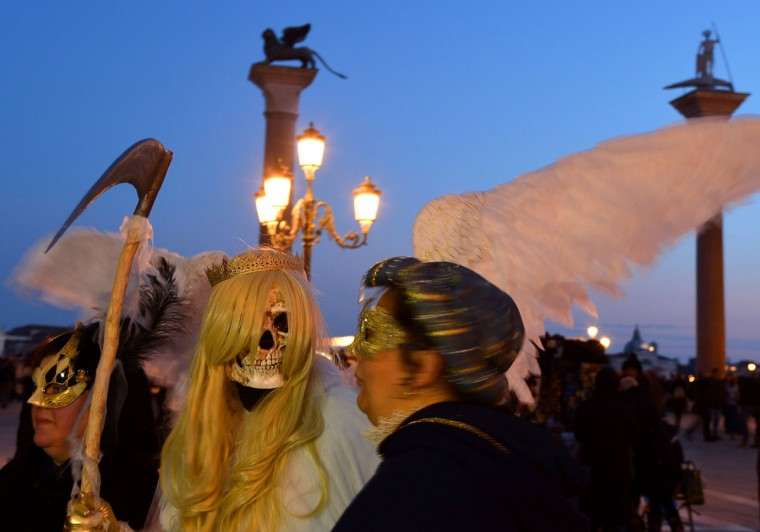 Costumed revelers walk on St Mark's square during the carnival on February 7, 2015 in Venice. (VINCENZO PINTO/AFP/Getty Images)