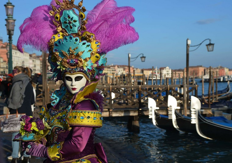 A costumed reveler poses near gondolas during the carnival on February 7, 2015 in Venice. (VINCENZO PINTO/AFP/Getty Images)