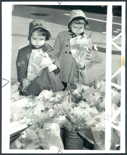 April 12, 1960: Monica, 2-1/2, and and Marion, 4-1/2 Petrik buy flowers for Easter at Lexington and Charles Streets display. Photo taken by Baltimore Sun Staff Photographer Albert D. Cochran.