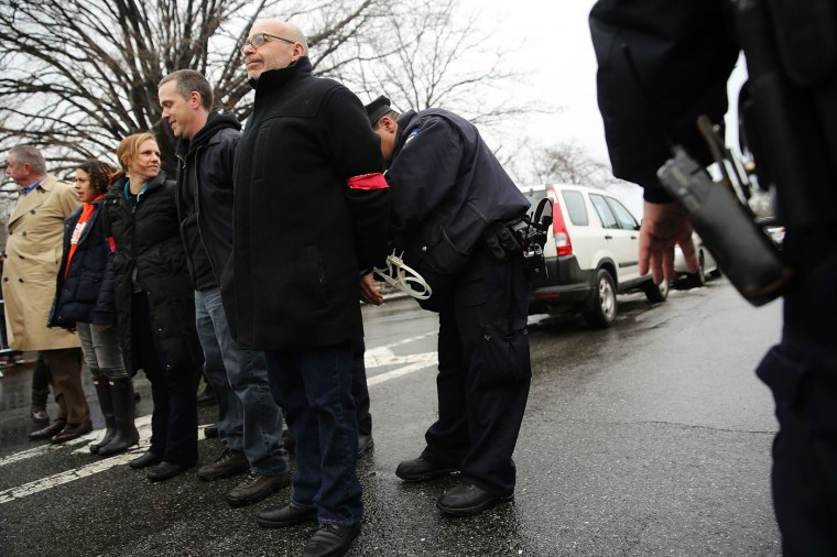 People are arrested in front of the Vegas Auto Spa, a car wash that has become a focal point for labor and union rights, during a rally on March 4, 2015 in the Brooklyn borough of New York City. Hundreds of people joined the morning rally where a small number of activists blocked a road outside of the car wash and were arrested by police. Eight workers from the popular car wash have filed a federal lawsuit against their employer and have been on strike for over two months over issues of pay, hours, safe working conditions and the right to join a union. The suit alleges that they were paid less than minimum wage and it demands $600,000 in overtime and other back wages. (Photo by Spencer Platt/Getty Images)