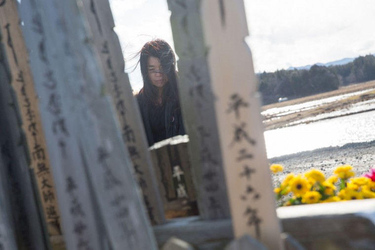 Noriko Iwasaki, 45, who lost her uncle by tsunami, prays on March 11, 2015 in Ukedo, Fukushima prefecture, Japan. On March 11 Japan commemorates the fourth anniversary of the magnitude 9.0 earthquake and tsunami that claimed more than 18,000 lives, and subsequent nuclear disaster at the Fukushima Daiichi Nuclear Power Plant. (Photo by Ken Ishii/Getty Images)