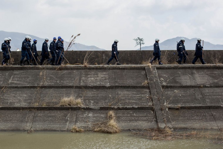 Police walk along a seawall as they prepare to search for the remains of tsunami victims or any identifying personal items on March 11, 2015 in Rikuzentakata, Japan. Police from Iwate prefecture continue to search for remains, and personal items that could be returned to loved ones on the 11th of every month. On March 11 Japan commemorates the fourth anniversary of the magnitude 9.0 earthquake and tsunami that claimed more than 18,000 lives, and subsequent nuclear disaster at the Fukushima Daiichi Nuclear Power Plant. (Photo by Chris McGrath/Getty Images)