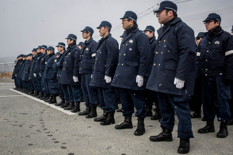 Police listen to instructions as they prepare to search for the remains of tsunami victims or any identifying personal items on March 11, 2015 in Rikuzentakata, Japan. Police from Iwate prefecture continue to search for remains, and personal items that could be returned to loved ones on the 11th of every month. On March 11 Japan commemorates the fourth anniversary of the magnitude 9.0 earthquake and tsunami that claimed more than 18,000 lives, and subsequent nuclear disaster at the Fukushima Daiichi Nuclear Power Plant. (Photo by Chris McGrath/Getty Images)