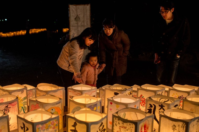 People look at paper lanterns during a memorial service for tsunami victims at the Yuriage Junior High School on March 11, 2015 in Natori, Japan. On March 11 Japan commemorates the fourth anniversary of the magnitude 9.0 earthquake and tsunami that claimed more than 18,000 lives, and subsequent nuclear disaster at the Fukushima Daiichi Nuclear Power Plant. (Photo by Chris McGrath/Getty Images)