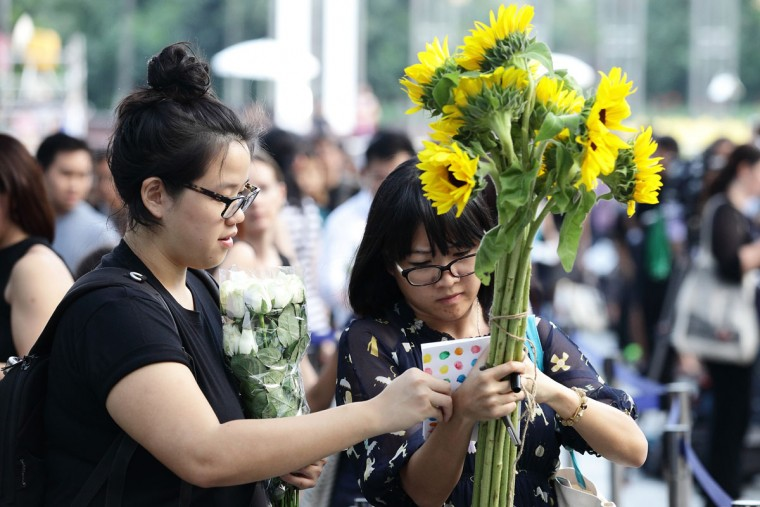 A woman writes a tribute while holding a bunch of sunflowers as she waits in the queue outside the Istana main gate following the passing of former Prime Minister Lee Kuan Yew on March 23, 2015 in Singapore. Former Prime Minister, Lee Kuan Yew, 91, died last night at Singapore General Hospital after spending several weeks in critical condition after being admitted for pnemonia on February 5. Lee Kuan Yew served as the first Prime Minister of Singapore when it gained rule from Britain in 1959 and until he stepped down in 1990. (Photo by Suhaimi Abdullah/Getty Images)