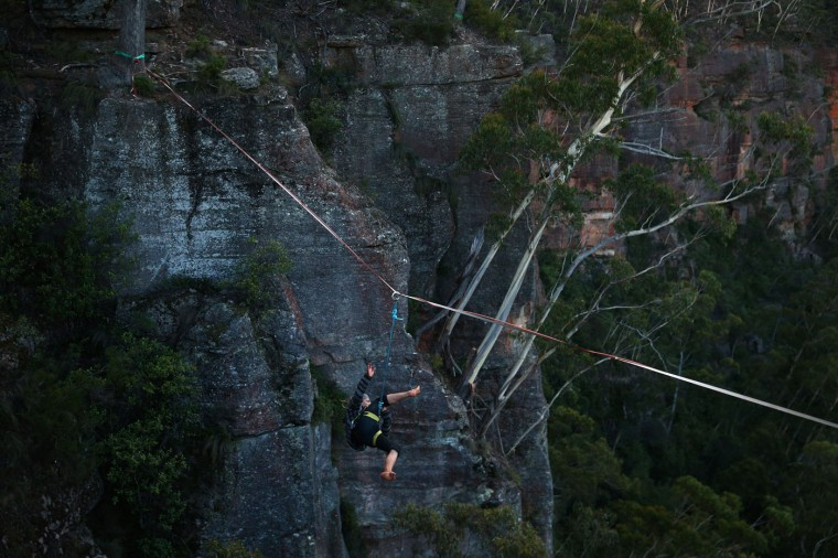 Joseph Huard of Canada falls as he walks along a highline rigged between cliffs at Corroboree Walls in Mount Victoria on March 7, 2015 in the Blue Mountains, Australia. (Photo by Cameron Spencer/Getty Images)