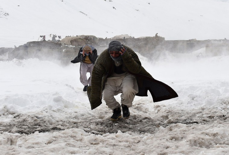 Afghan survivors of an avalanche run to get relief goods distributed by an Afghan army helicopter in the Paryan district of Panjshir province, north of Kabul on March 1, 2015. Afghan President Ashraf Ghani February 28 pledged to set up a relief fund for the victims of avalanches that claimed over 280 lives, and called for international help with the relief effort. (Shah Marai/AFP/Getty Images)