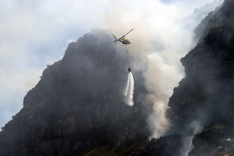 A firefighting helicopter dumps water on part of a large bush fire raging in the mountains on the Cape Peninsula in the greater Cape Town area. (RODGER BOSCH/AFP/Getty Images)