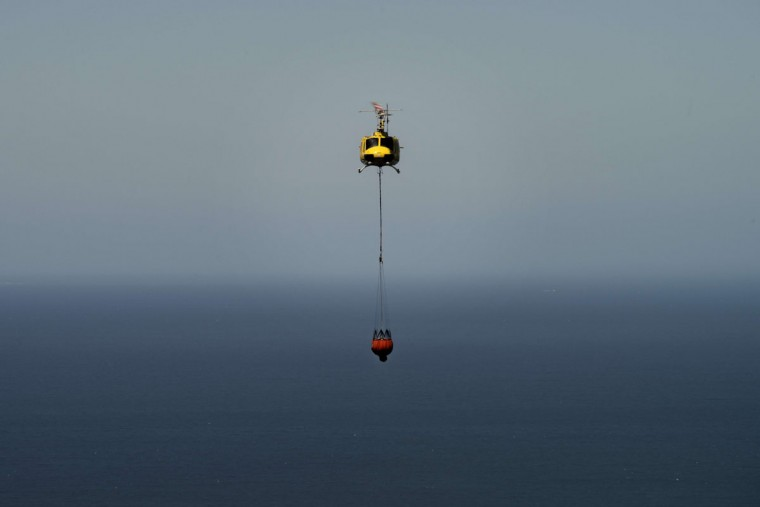 A fire-fighting helicopter flies, with the sea in the background, to dump water on part of a large bush fire raging in the mountains on the Cape Peninsula, on March 2, 2015, in the greater Cape Town area. (RODGER BOSCH/AFP/Getty Images)