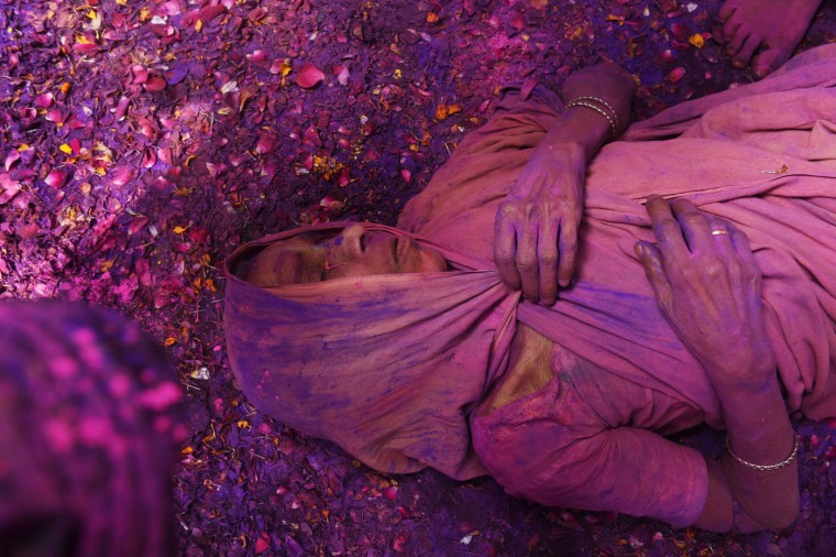 "An Indian widow lies on a patio floor covered in flower petals and colored powder as they celebrate Holi or ""festival of colors"" in Vrindavan on March 3, 2015. Widows congregated on a small patio of the ashram in which they live and danced and played with colored powder to celebrate the occasion. The widows of this and other ashrams in this northern town are sponsored by the NGO, Sulabh International which funds most of their needs. Shunned from society when their husbands die, not for religious reasons, but because of tradition, many Indian widows have been otracized from society and no longer live with their families and are forced to beg for food. Almost 2,000 of the estimated 34 million widows currently living in India live in Vrindavan and benefit from the welfare extended by the NGO. (Roberto Schmidt/AFP/Getty Images)"