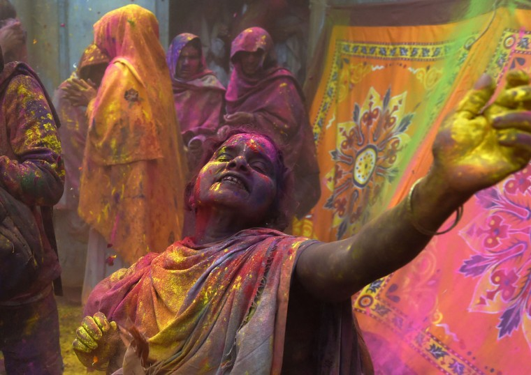"An Indian widow dances as they celebrate Holi or ""festival of colors"" in Vrindavan on March 3, 2015. Widows congregated on a small patio of the ashram in which they live and danced and played with colored powder to celebrate the occasion. The widows of this and other ashrams in this northern town are sponsored by the NGO, Sulabh International which funds most of their needs. Shunned from society when their husbands die, not for religious reasons, but because of tradition, many Indian widows have been otracized from society and no longer live with their families and are forced to beg for food. Almost 2,000 of the estimated 34 million widows currently living in India live in Vrindavan and benefit from the welfare extended by the NGO. (Roberto Schmidt/AFP/Getty Images)"