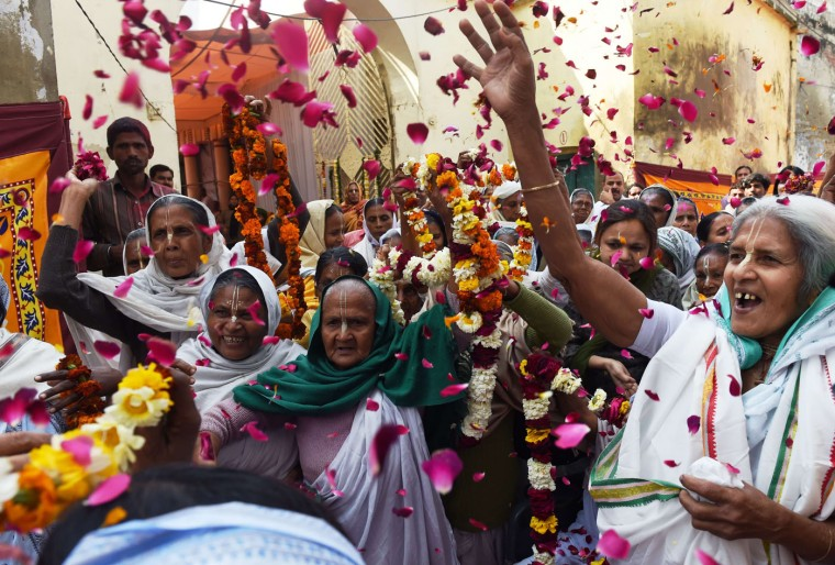 "Indian widows throw petals as a sign of welcome on the arrival of Bindeshwar Pathak, founder of NGO Sulabh International which funds some Indian widows sheltering in ashrams, before playing Holi or the 'festival of colours' in Vindravan on March 3, 2015. Shunned from society when their husbands die, not for religious reasons, but because of tradition many Indian widows were otracized from society, no longer lived with their families and were forced to beg for food. Almost 2,000 of the estimated 34 million widows currently living in India live in Vrindavan and benefit from the welfare extended by the NGO. The widows were attending a ceremony where they celebrate Holi or ""festival of colors"". (Roberto Schmidt/AFP/Getty Images)"