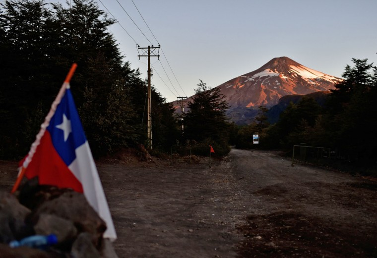 A Chilean national flag is seen with the Villarrica volcano in the background, near Villarrica in southern Chile, showing no visible signs of activity just a couple of hours after it erupted on March 3, 2015. The Villarrica erupted early Tuesday, spewing fiery plumes of lava into the night sky and forcing the evacuation of some 3,600 people in nearby towns. In its first major eruption in 15 years, the Villarrica volcano, prompted authorities to declare a red alert, the National Emergency Office said. But within about seven hours the eruption calmed, and there were no longer any visible signs of activity. (Martin Bernetti/AFP/Getty Images)