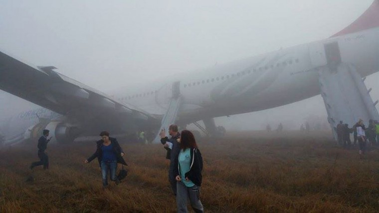Passengers walk away from a Turkish Airlines plane after it skidded off the runway while landing at Kathmandu airport in the Nepalese capital Kathmandu on March 4, 2015. Aviation officials said no one on board was injured, although one witness described how terrified passengers leapt from their seats as the cabin filled with smoke after the plane skidded to a halt. (Dikesh Malhotra/AFP/Getty Images)