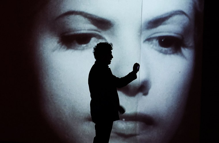 """A man uses his phone to take pictures as a clip from a movie is projected on wall during a press preview of """"Under The Mexican Sky: Gabriel Figueroa, Art and Film exhibition"""" at The El Museo del Barrio in New York on March 3, 2015. The exhibition, which will run from March 4 to June 27 2015, is organized to celebrates the successes and legacy of Gabriel Figueroa (1907-1997), a Mexican cinematographer who worked both in Mexico and Hollywood. (Jewel Samad/AFP/Getty Images)"""