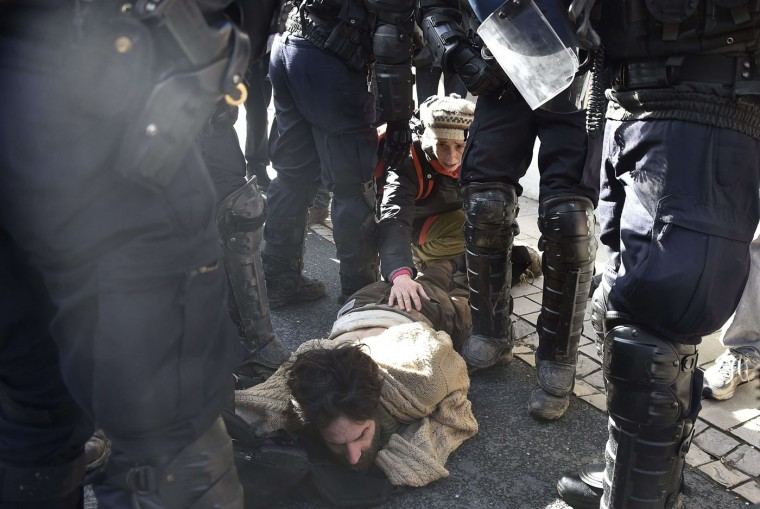"""An environmental activist blocking the site of a proposed dam in the Sivens forest, comforts a colleague after being arrested following clashes between activists and Gendarmes on March 4, 2015 in the nearby town of Gaillac, southwestern France. The activists tried to force a blockade by pro-dam farmers in order to supply foods to the Zadists the name given to the activists occupying the site """"zone to defend,"""" or ZAD. Farmers argue that the dam will provide much-needed irrigation for their fields. Anti-dam say the proposed dam poses a huge environmental threat to the biodiverse Sivens wetland. (Pascal Pavani/AFP/Getty Images)"""