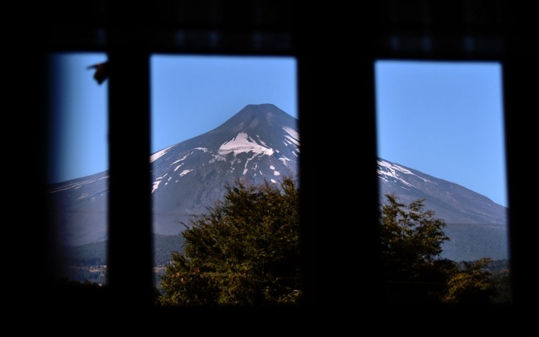 View of the Villarrica volcano, from Pucon, some 800 km south of Santiago, showing no visible signs of activity on March 5, 2015. The Villarrica erupted early Tuesday, spewing fiery plumes of lava into the night sky and forcing the evacuation of some 3,600 people in nearby towns. In its first major eruption in 15 years, the Villarrica volcano, prompted authorities to declare a red alert, the National Emergency Office said. Chile keeps the red alert two days after the Villarrica volcano erupted but reduced the risk area from 10 to 5 km. (Martin Bernetti/AFP/Getty Images)