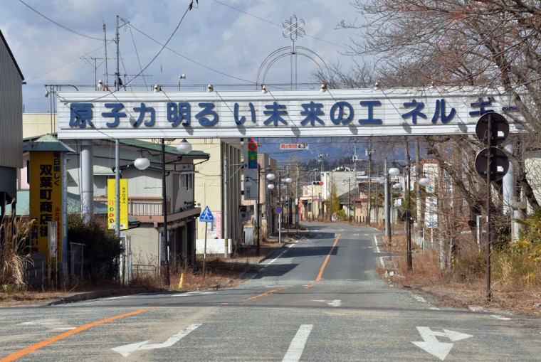 "A signboard which reads ""Nuclear power: the energy for a bright future"" over a main street of Futaba town near crippled Tokyo Electric Power Co (TEPCO) Fukushima Dai-ichi nuclear plant in Futaba town in Fukushima prefecture. A Japanese town that has been evacuated since the 2011 Fukushima nuclear disaster has decided to remove street signs trumpeting the benefits of atomic power, an official said on March 10, 2015. Futaba town, which plays host to the crippled Fukushima Dai-ichi nuclear power plant, has earmarked cash to remove huge signboards erected in 1988 and 1991, a town official told AFP. (AFP Photo/Yoshikazu Tsuno)"