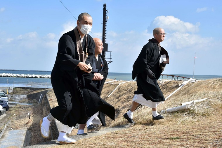 Buddhist monks arrive at Soma in Fukushima prefecture to offer prayers for tsunami and earthquake victims on March 11, 2015 on the fourth anniversary day of massive earthquake and tsunami hit northern Japan. The 9.0 magnitude earthquake in 2011 sent a huge wall of water into the coast of the Tohoku region, splintering whole communities, ruining swathes of prime farmland and killing nearly 19,000 people. (AFP Photo/Yoshikazu Tsuno)