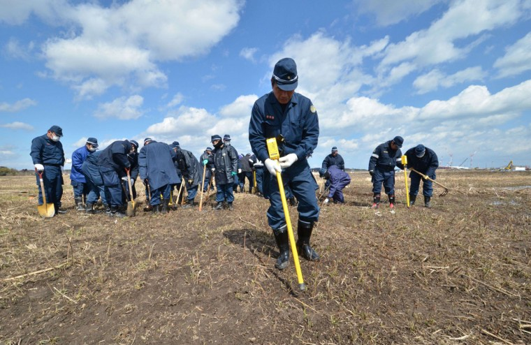 Police officers search for the remains of missing people with metal detector at Namie, near the striken TEPCO's Fukushima Dai-ichi nuclear plant in Fukushima prefecture on March 11, 2015 on the fourth anniversary day of massive earthquake and tsunami hit northern Japan. The 9.0 magnitude earthquake in 2011 sent a huge wall of water into the coast of the Tohoku region, splintering whole communities, ruining swathes of prime farmland and killing nearly 19,000 people. (AFP Photo/Yoshikazu Tsuno)
