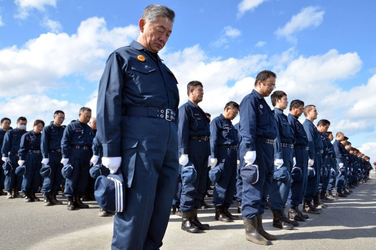 Police officers observe a moments silence for victims of the 2011 quake-tsunami disaster during a memorial ceremony at Namie, near TEPCO's Fukushima Dai-ichi nuclear plant in Fukushima prefecture on March 11, 2015. Japan marked the fourth anniversary on March 11 of the quake-tsunami disaster that swept away thousands of people and sparked a nuclear crisis, a tragedy that has left visible scars on the landscape and continues to wreak misery for many. (AFP Photo/Yoshikazu Tsuno)