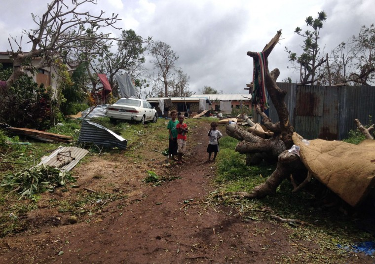 This handout photo taken on March 14, 2015 and released to AFP on March 15 by Australian Red Cross shows children standing next to debris as residents deal with the damage to their homes in Seaside, near the Vanuatu capital of Port Vila. Vanuatu's president made an emotional appeal for international assistance after his island nation was hit by a calamity of a cyclone, wreaking devastation in what is feared to be one of the region's worst weather disasters. Vanuatu declared a state of emergency on March 15, saying six people were confirmed dead as a result of the monster storm with the toll expected to rise. (Chris McCowage/Australian Red Cross/AFP/Getty Images)