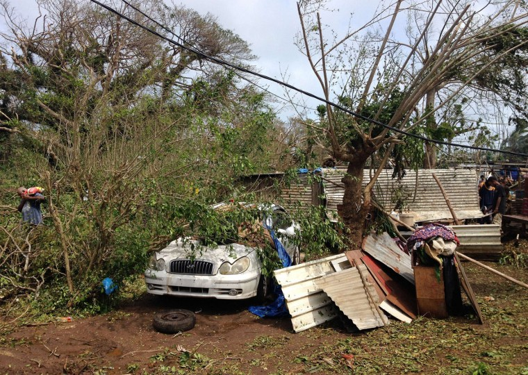 This handout photo taken on March 14, 2015 and released to AFP on March 15 by Australian Red Cross shows people clearing up debris and dealing with the damage to their homes and property in Seaside, near the Vanuatu capital of Port Vila. Vanuatu's president made an emotional appeal for international assistance after his island nation was hit by a calamity of a cyclone, wreaking devastation in what is feared to be one of the region's worst weather disasters. Vanuatu declared a state of emergency on March 15, saying six people were confirmed dead as a result of the monster storm with the toll expected to rise. (Chris McCowage/Australian Red Cross/AFP/Getty Images)