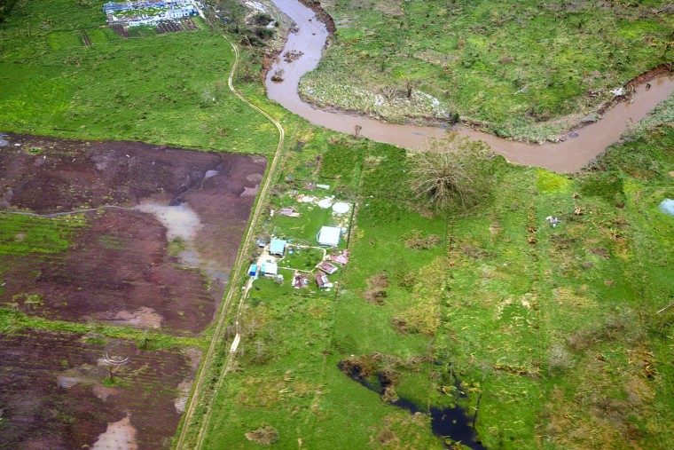 """This handout photo taken and received on March 15, 2015 by CARE Australia shows an aerial photo of a home decimated by Cyclone Pam in the Vanuatu town of Efate. Cyclone-devastated Vanuatu declared a state of emergency on March 15 as relief agencies scrambled to get help to the remote Pacific nation amid reports entire villages were """"blown away"""" when the monster storm swept through. (Tom Perry/CareAFP/Getty Images)"""