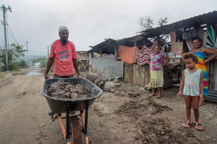 """This handout photo taken and received on March 15, 2015 by UNICEF Pacific shows a resident clearing mud and other debris outside homes after the area was badly damaged by Cyclone Pam, outside the Vanuatu capital of Port Vila. Cyclone-devastated Vanuatu declared a state of emergency on March 15 as relief agencies scrambled to get help to the remote Pacific nation amid reports entire villages were """"blown away"""" when the monster storm swept through. (UNICEF Pacific/AFP/Getty Images)"""