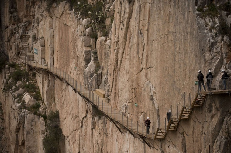 "Journalists walk during a visit to the foot-path ""El Caminito del Rey"" (King's little path) a narrow walkway hanging and carved on the steep walls of a defile in Ardales near Malaga on March 15, 2015. (Jorge Guerrero/AFP/Getty Images)"