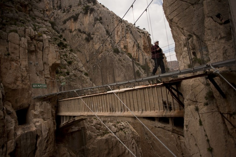 "A man crosses a footbridge during a visit to the foot-path ""El Caminito del Rey"" (King's little path) a narrow walkway hanging and carved on the steep walls of a defile in Ardales near Malaga on March 15, 2015. (Jorge Guerrero/AFP/Getty Images)"